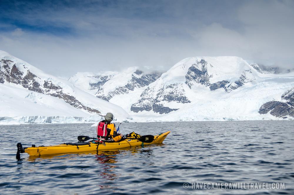 A kayaker heads towards the scenic mountains at Neko Harbour, Antarctica.