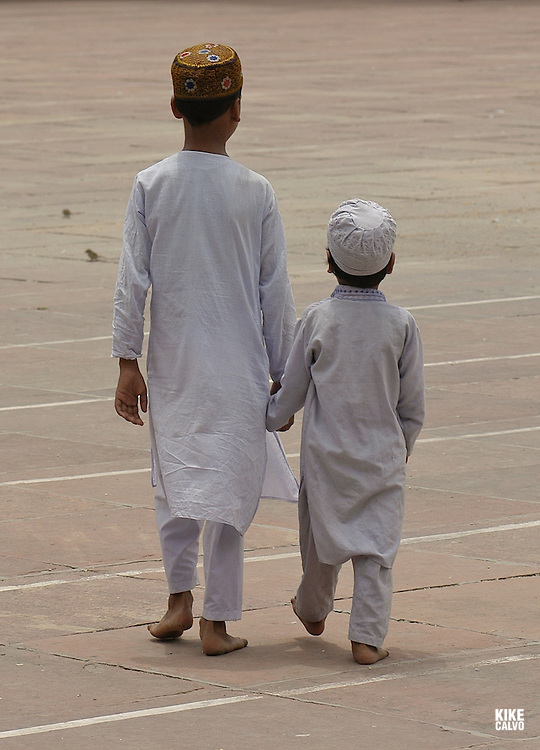 Two muslim brothers walk holding hands