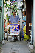 """Mar 23, 2009 -- BANGKOK, THAILAND:  An ice cream vendor walks down an alley in Ban Krua. There aren't many streets in this part of Bangkok, mostly alleys that are barely wide enough for two people to pass. The Ban Krua neighborhood of Bangkok is the oldest Muslim community in Bangkok. Ban Krua was originally settled by Cham Muslims from Cambodia and Vietnam who fought on the side of the Thai King Rama I. They were given a royal grant of land east of what was then the Thai capitol at the end of the 18th century in return for their military service. The Cham Muslims were originally weavers and what is known as """"Thai Silk"""" was developed by the people in Ban Krua. Several families in the neighborhood still weave in their homes.     Photo by Jack Kurtz"""