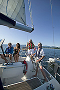 Two couples enjoy a leisure sail just off the coast of Powell River, in the Strait of Georgia. An ocean playground featuring many small islands, a view of the townsite of Powell River and a relatively consistent breeze make for perfect conditions to explore this region of the Sunshine Coast.