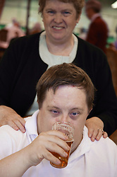 Young man with Downs Syndrome drinking beer at a bowls event held at Solihull Indoor Bowls Centre,