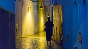 RABAT, MOROCCO - 16th October 2015 - Silhouette figures walking through a narrow archway street in the old Rabat Medina at night, Morocco.