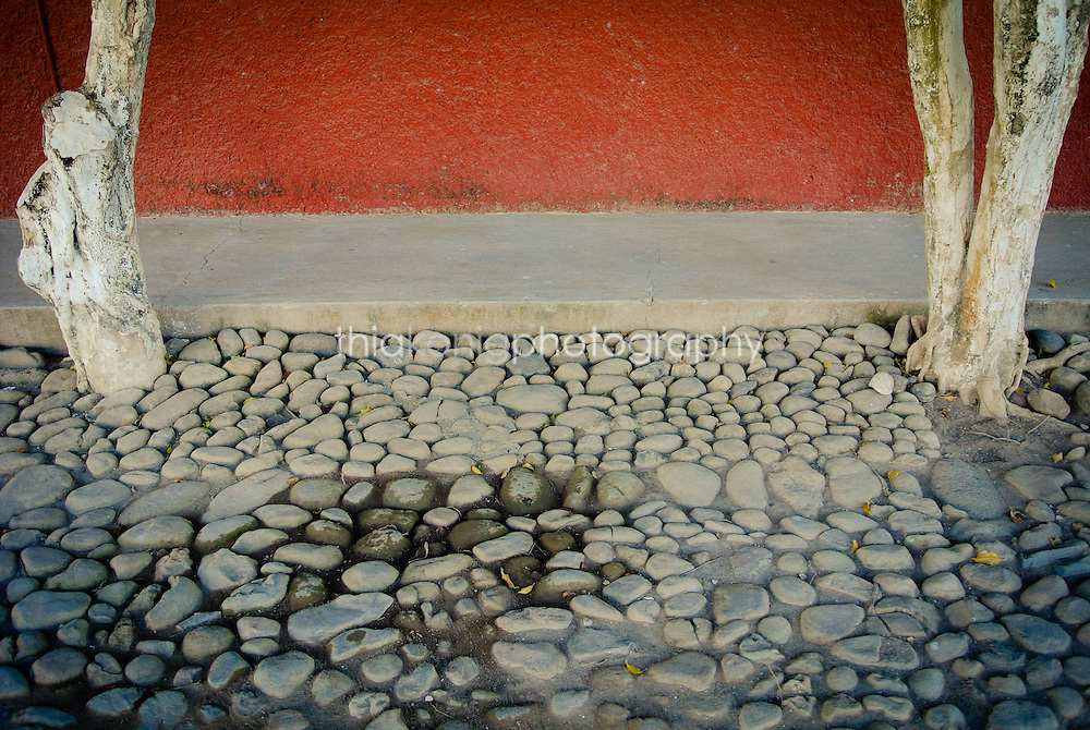 Detail of cobblestone street with red wall and trees on side, San Blass, Mexico