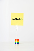 Sticky notepaper with Italian text meaning Milk clipped to a multicolored card holder