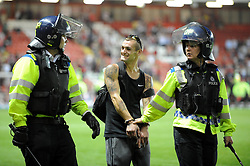 A fan is escorted of the pitch by Riot Police  - Photo mandatory by-line: Dougie Allward/JMP - Tel: Mobile: 07966 386802 04/09/2013 - SPORT - FOOTBALL -  Ashton Gate - Bristol - Bristol City V Bristol Rovers - Johnstone Paint Trophy - First Round - Bristol Derby