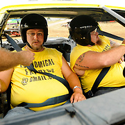"Kris Wilson/News Tribune.Jerry ""Porkchop"" Kennard, left, and John Love tighten up the safety belts before taking the track for the first heat of the Figure 8 Scramble at the Jefferson City Jaycees Cole County Fair on Friday."