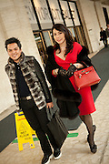 A woman in red and a man with a fur vest leave the fashion show.
