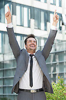 Successful businessman pointing upwards outside office building