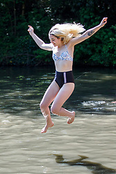 © Licensed to London News Pictures. 07/05/2018. London, UK. Jess Lidgerwood swims in Hampstead Heath Mixed Bathing Pond in north London as temperatures hit 28C on the hottest May bank holiday since 1999 on Monday, May 7, 2018. Photo credit: Tolga Akmen/LNP