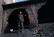 A miner operating the coal extraction conveyor at a regional coal mine. 75% of China's growing energy needs come from coal, the cheapest and most polluting form of energy. China is the world's largest coal producer. Seven of the world's ten most polluted cities are in China, largely due to coal use and the country's dilapidated heavy industries.<br /> D&agrave;t&oacute;ng, Shanxi Province, China. 11/11/2005<br /> Photo &copy; J.B. Russell