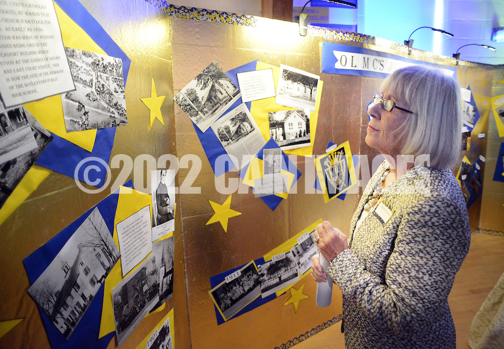 Jeanne Jourdan, of Cassopolis, Michigan and a 1954 graduate of Mt. Carmel looks at a board of pictures from the school's 140 year history during Our Lady of Mt. Carmel School's 140th Anniversary celebration Saturday, April 9, 2016 at the school in Doylestown, Pennsylvania.  (Photo by William Thomas Cain)