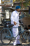 A man in traditonal dress and turban with his bicycle in Jodhpur, Rajasthan, India