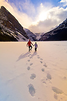 A father and son walking on Lake Louise with the Chateau Lake Louise Hotel in the background, Banff National Park, Alberta, Canada