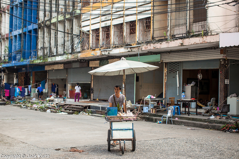 """03 DECEMBER 2012 - BANGKOK, THAILAND:  A food vendor pushes his cart through the """"Washington Square"""" district in Bangkok. Workers live in the buildings they are demolishing until the buildings are completely uninhabitable. Washington Square was a notorious adult """"entertainment"""" and red light district on Sukhumvit Soi 22 in Bangkok. Many of the bars and massage parlors catered in the district to older American and European men and opened in the 1960's when Bangkok was a """"R&R"""" destination for American servicemen in Vietnam. It's being torn down to make way for new high rise hotels and condominiums.        PHOTO BY JACK KURTZ"""