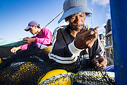 30 APRIL 2013 - MAHACHAI, SAMUT SAKHON, THAILAND:   Burmese workers repair a fishing nets in the port of Mahachai, Samut Sakhon province, Thailand. The Thai fishing industry is heavily reliant on Burmese and Cambodian migrants. Burmese migrants crew many of the fishing boats that sail out of Samut Sakhon and staff many of the fish processing plants in Samut Sakhon, about 45 miles south of Bangkok. Migrants pay as much $700 (US) each to be smuggled from the Burmese border to Samut Sakhon for jobs that pay less than $5.00 (US) per day. There have also been reports that some Burmese workers are abused and held in slavery like conditions in the Thai fishing industry.         PHOTO BY JACK KURTZ