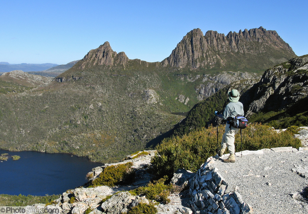 Bushwalkers enjoy Cradle Mountain (1545 m or 5069 ft)and Dove Lake, in Cradle Mountain - Lake Saint Clair National Park, Tasmania, Australia. The Tasmanian Wilderness was honored as a UNESCO World Heritage Site in 1982, expanded in 1989. The most extensive dolerite formations in the world dominate the landscape of Tasmania, where magma intruded into a thin veneer of Permian and Triassic rocks over perhaps a million years during the Jurassic breakup of supercontinent Gondwana in the Southern Hemisphere, forming vast dolerite/diabase sills and dike swarms. (North American geologists use the term diabase instead of dolerite to refer to the fresh, unaltered rock.)