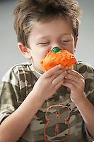 Young boy eating cupcake half length