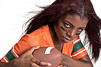 Portrait of young woman playing american football.