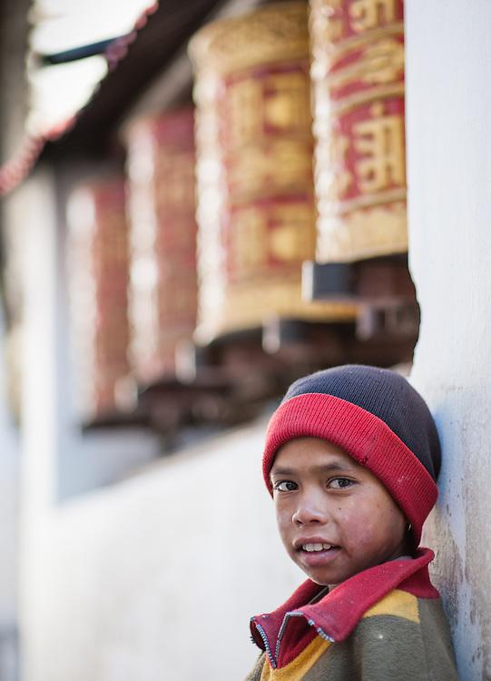 Boy in front of huge prayer wheels (Nepal)