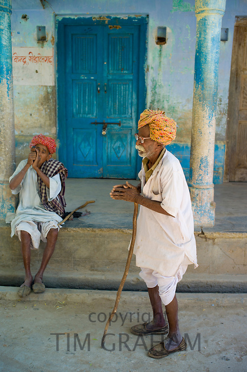 Indian local men in Rajasthani turbans, one of them smoking tobacco from Chillam clay pipe at Nimaj village, Rajasthan, India