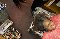 Harlem, New York, USA - March 24. The deceased woman Bernice McCants, 72, lays down on a stretcher in the chapel of the Isaiah Owens Funeral Home before being placed in her casket on March 24, 2008 in Harlem, New York, USA. Next to her, on the left, are some tools used by the funeral home director Isaiah Owens for the preparation of the body. These include make-up, needles, liquid tissue (botox), and oil (for the face).