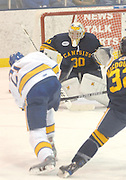 Canisius Griffin goalkeeper Dan Morrison (#30) prepares for a shot from a charging LSSU Lakers Will Acton (#21) during the second period of the Griffins 5-4 loss to Lakers Friday night in Sault Ste. Marie, MI.