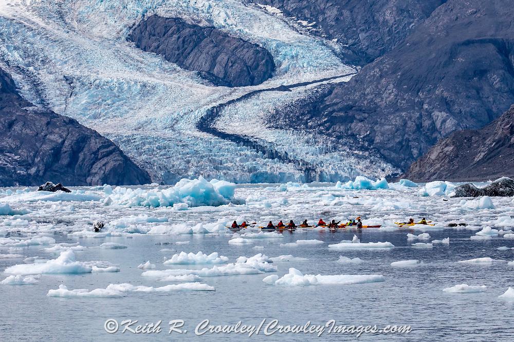 Kayakers paddle through ice floes near Valdez, Alaska.