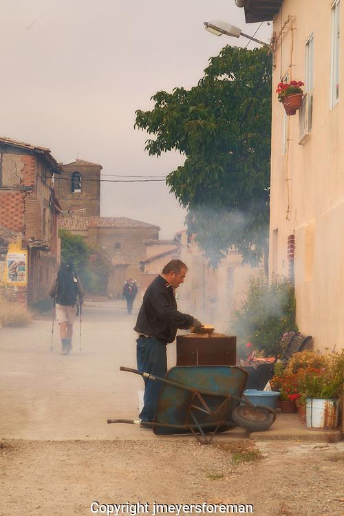 pilgrims walk along the Camino to Santiago de Compostela while life goes on, a gentleman smokes the Pimiento fresh from his garden