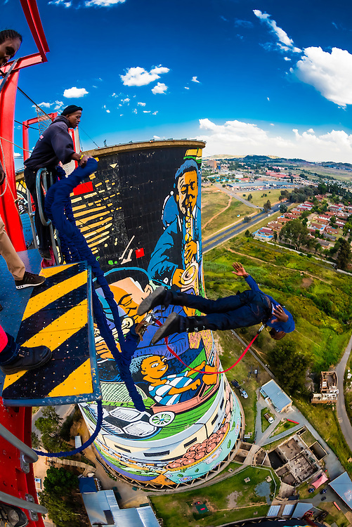 Man jumps off the 100 meter (328 foot) bungee jump at Orlando Towers at the decomissioned Orlando Power Station (former coal fired power station), Soweto,