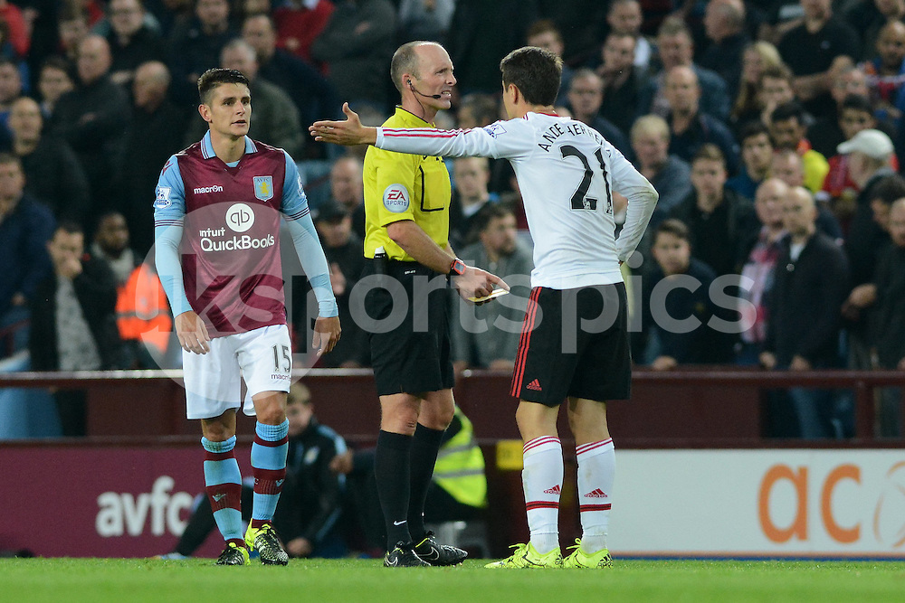 Manchester United's Ander Herrera argues his yellow card with referee Mike Dean during the Barclays Premier League match between Aston Villa and Manchester United at Villa Park, Birmingham, England on 14 August 2015. Photo by Garry Griffiths.
