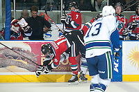 KELOWNA, CANADA - OCTOBER 7: Tate Coughlin #18 of Kelowna Rockets falls to the ice after a check by the Swift Current Broncos on October 7, 2014 at Prospera Place in Kelowna, British Columbia, Canada.  (Photo by Marissa Baecker/Getty Images)  *** Local Caption *** Tate Coughlin;