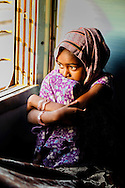 A young girl sitting thoughtfully in a sleeper class train, india