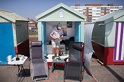 © Licensed to London News Pictures. 22/04/2019. Brighton and Hove, UK. A man reads his newspaper in a beach hut on the Western Esplanade at Hove, West Sussex as most of the UK enjoys record breaking high Easter weekend temperatures. Photo credit: Peter Macdiarmid/LNP