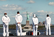 Sailors and US Marines line the rails of the USS Kennedy aircraft carrier as the ship sails up the Hudson River into New York City.