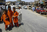 Three school childern in uniform and one student from an Islamic madrasa at Landi Kotal village, Pakistan on Monday Aug. 7, 2006. Landi Kotal is on the way to the Torkham border post in Peshawar. Torkham is the most important border crossing on the northeast transit route between Afghanistan and Pakistan. The Torkham border processes around 1,400 vehicles per day, 79% of which is heavy truck and cargo traffic. Long lines of vehicles and oil tankers can also be seen across the Torkham border between Afghanistan and Pakistan as Afghan officials stop them for fear of terrorism.