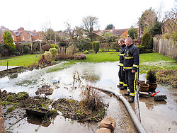 Two firemen check out the pumping operation in a flooded garden in Marlow Thames Valley, United Kingdom. Tuesday, 18th February 2014. Picture by Max Nash / i-Images