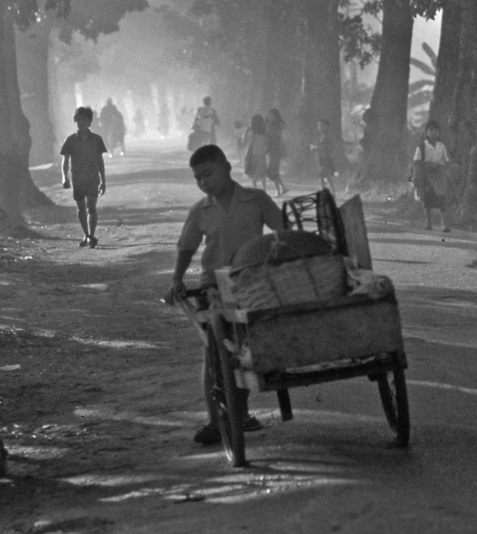 Lao boy pushes market cart on dusty road in rural Vientiane.