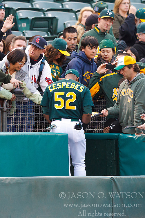 April 9, 2012; Oakland, CA, USA; Oakland Athletics center fielder Yoenis Cespedes (52) signs autographs before the game against the Kansas City Royals at O.co Coliseum.  Oakland defeated Kansas City 1-0. Mandatory Credit: Jason O. Watson-US PRESSWIRE