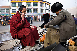 Tibet New Year - China - Edward Wong<br /> A monk from Rongwo monastery  (Longwu in Chinese) waits for repair of his boots in Rebkong (Tongren in Chinese), Qinghai province in China, February 24, 2009. Photo by Shiho Fukada for The New York Times