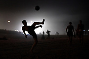 A man plays soccer at night on Copacabana beach during the 2016 Rio Summer Olympics in Rio de Janeiro, Brazil.