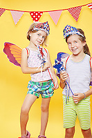 2 sisters wearing red white and blue tiara's holding magic wands against a yellow seamless<br /> Photographed at the Photoville Photo Booth September 20, 2015