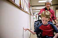 JEROME A. POLLOS/Press..Alex Hess feels the wall as he is pushed down the hall of John Brown Elementary in Rathdrum by his life skills aide, Cheryl Ashurst, on Oct. 16. Hess is completely blind and uses his sense of touch and hearing to help give him a sense of direction.