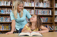 School girl reading book with teacher in library