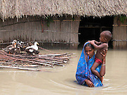 A viialge woman carries his little son through floodwaters after their house is inundated by floodwater at Birshing village, about 313 kilometers southwest of Gauhati, the capital city of Northeastern Indian state, Assam, Wednesday, June 30, 2004..Floodwaters of the Asia'a one of the largest river, Brahmaputra and its 35 tributaries have affected more than one million in all of Indian subcontinent and disrupted communication in many parts of the India and Bangladesh, sources said. (AP Photo/ Shib Shankar Chatterjee).