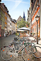 Row of colorful bikes in the old European town of Heidelberg Germany amid color buildings and old architecture.