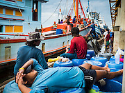 01 OCTOBER 2015 - MAHACHAI, SAMUT SAKHON, THAILAND:  Members of a fishing crew relax after their trawler returned to port in Mahachai, one of Thailand's largest fishing ports. Thailand's fishing industry had been facing an October deadline from the European Union to address issues related to overfishing and labor practices. Failure to adequately address the issues could have resulted in a ban on Thai exports to the EU. In September Thai officials announced that they had secured an extension of the deadline. Officials did not say how much extra time they had to meet the EU goals. Thailand's overall annual exports to the EU are between 23.2 billion Thai Baht and 30 billion Thai Baht (US$645 million to US $841 million). Thailand's total fish exports were worth about 110 billion baht in 2014.   PHOTO BY JACK KURTZ
