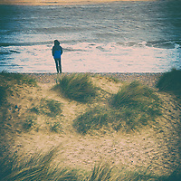 Figure of teen girl standing alone looking out to a stormy sea