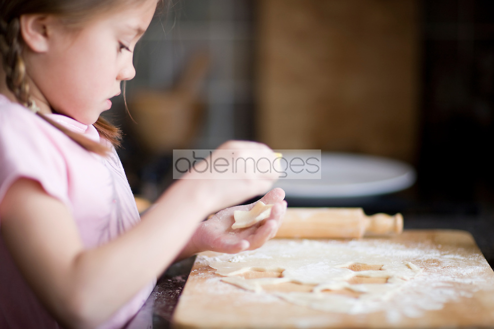 Close up of young girl cutting shapes from baking dough