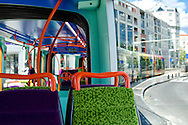 A brightly painted tram running beside the buildings opposite the river Lez in Quartier Port-Marianne, Montpellier.