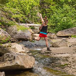 A woman explores Haley Brook near Saddleback Lake in Dallas Plantation, Maine. High Peaks region, near Rangeley.